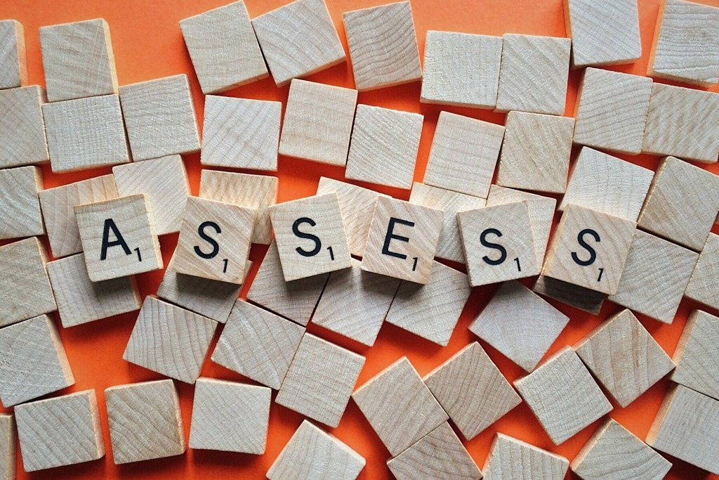 Pieces of scrabble board game with the word assess formed in the center.