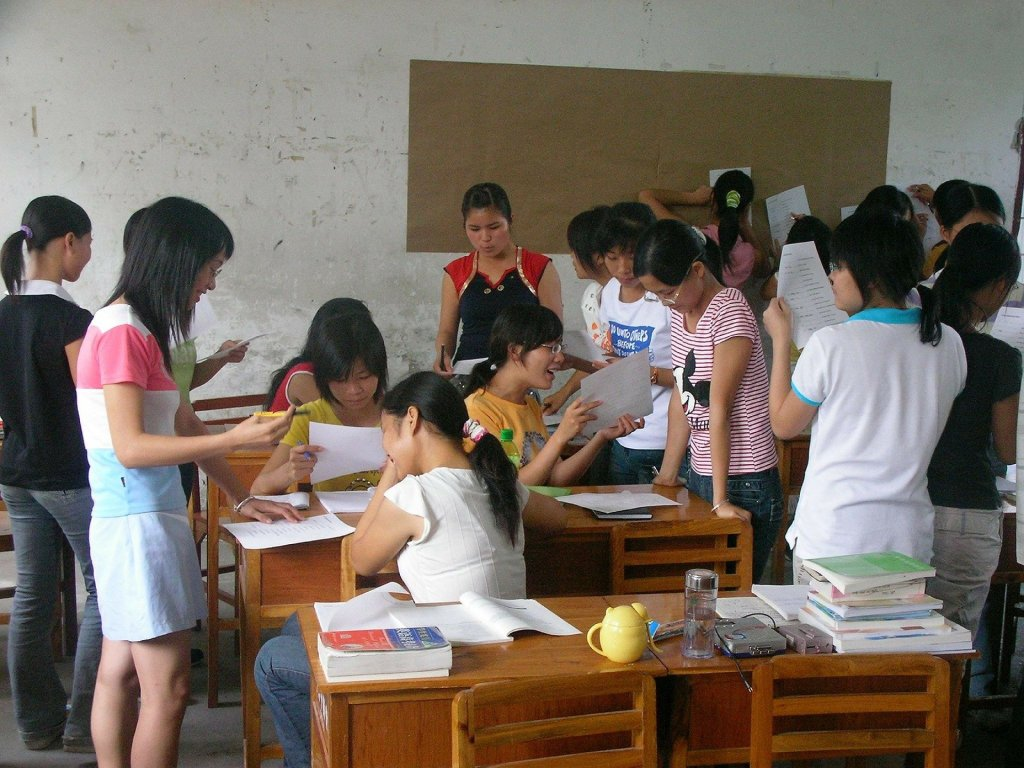 Group of teenager girls in a classroom enthusiastically discussing a problem.
